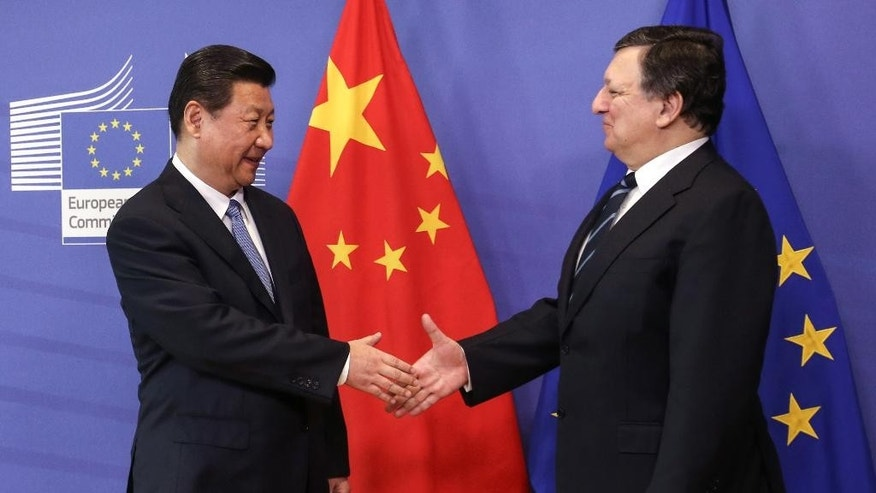 European Commission President Jose Manuel Barroso, right, shakes hands with China's President Xi Jinping, upon arrival at the European Commission headquarters in Brussels, Monday, March 31, 2014. China's President Xi Jinping is on a three-day visit to meet Belgian and EU officials. (AP Photo/Olivier Hoslet, pool)