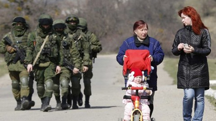 Women talk as they take a walk with a child while armed Russian servicemen follow them outside a Ukrainian military base in Perevalnoye, near the Crimean city of Simferopol. (Reuters)