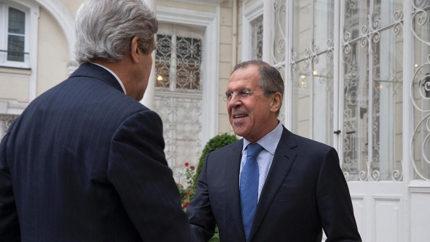 U.S. Secretary of State John Kerry, left, is greeted by Russian Foreign Minister Sergey Lavrov at the Russian Ambassador's residence for a meeting to discuss Ukraine, in Paris, Sunday March 30, 2014. Kerry traveled to Paris for the last minute meeting with Lavrov. (AP Photo/Jacquelyn Martin, Pool)