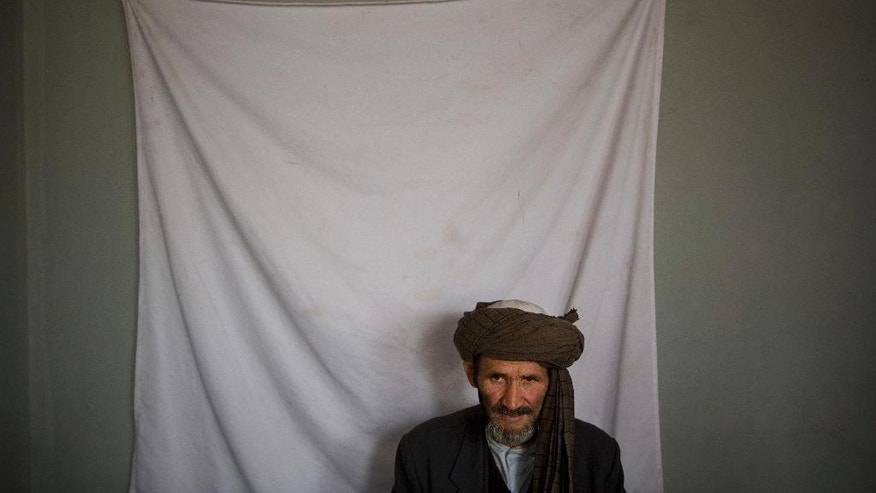 April 1, 2014: An Afghan man waits to have his picture taken for his registration card on the last day of voter registration for the upcoming presidential elections outside a school in Kabul, Afghanistan.