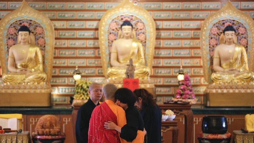 A Chinese relative of passengers on board the missing Malaysia Airlines Flight MH370 is comforted by a monk as she breaks into tears following prayers at a Buddhist temple in Petaling Jaya, Malaysia, Monday March 31, 2014. Relatives from China are in the country to seek answers of what happened to their loved one on board flight MH370. (AP Photo/Aaron Favila)