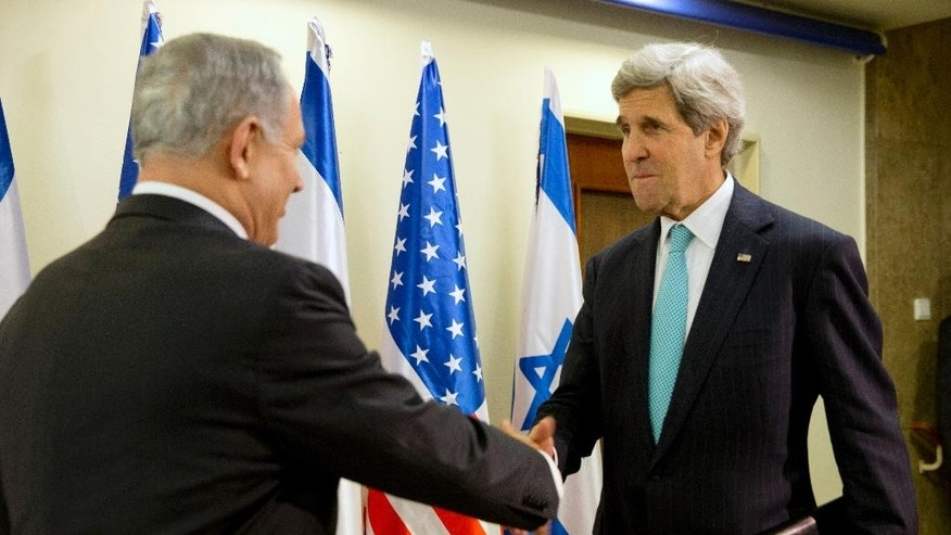 U.S. Secretary of State John Kerry, right, shakes hands with Israeli Prime Minister Benjamin Netanyahu in Jerusalem, Monday, March 31, 2014, for a previously unannounced stop in Israel to continue working on talks about the Middle East peace process. (AP Photo/Jacquelyn Martin, Pool)