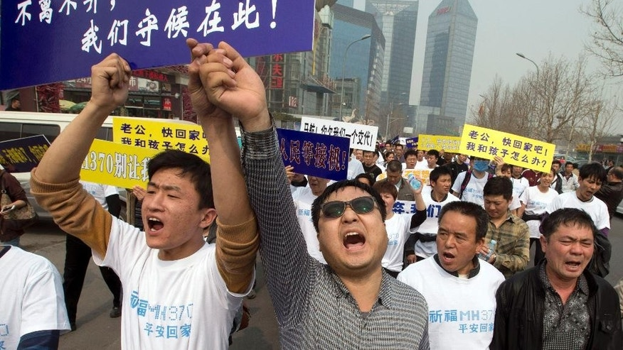 "FILE - In this Tuesday, March 25, 2014 file photo, Chinese relatives of passengers onboard the missing Malaysia Airlines plane, flight MH370, shout in protest as they march towards the Malaysia embassy in Beijing, China. Authorities have been forced on the defensive by the criticism, the most forceful of which has come from a group of Chinese relatives who accuse them of lying about - or even involvement in - the disappearance of Flight 370. The blue placard reads: ""We won't leave or ditch you, we will wait right here."" (AP Photo/Ng Han Guan, File)"