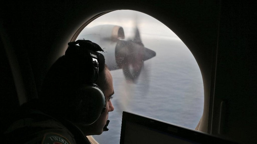 """FILE - In this Saturday, March 22, 2014 file photo, Flight officer Rayan Gharazeddine on board a Royal Australian Air Force AP-3C Orion, searches for the missing Malaysia Airlines Flight MH370 in southern Indian Ocean, Australia.  From """"All right, good night"""" to """"Good night, Malaysian three-seven-zero."""" Malaysia's tweak to the final words received from the cockpit of the missing jetliner would appear insignificant to the investigation or hunt for the plane. (AP Photo/Rob Griffith, Pool)"""
