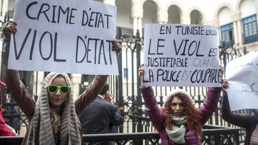 "Tunisian women demonstrate outside a Tunis courthouse where three police officers face charges of rape of a 27-year-old woman, Monday, March 31, 2014. The 27-year-old woman says three police officers stopped her in a car in September, and one of them held her fiance back while the other two raped her.  The police officers deny wrongdoing, and allege the couple had been engaged in ""immoral"" behavior. Posters read: at left, 'State Crime, State Rape', and at right 'Rape is right when police is guilty'. (AP Photo/Aimen Zine)"