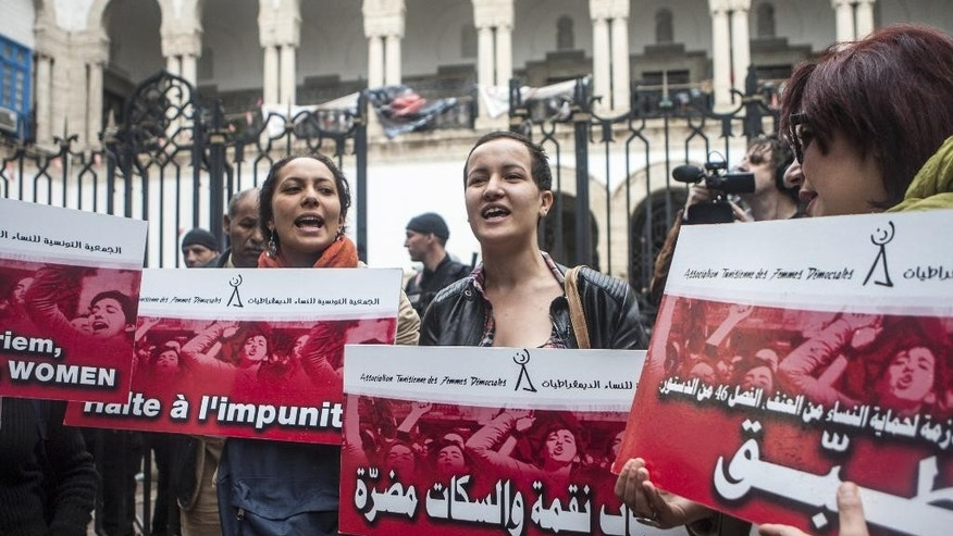 "Amina Sboui, center, a former Femen activist, and Tunisian women demonstrate outside a Tunis courthouse where three police officers face charges of the rape of a 27-year-old woman, Monday, March 31, 2014. The 27-year-old woman says three police officers stopped her in a car in September, and one of them held her fiance back while the other two raped her.  The police officers deny wrongdoing, and allege the couple had been engaged in ""immoral"" behavior. Poster in Arabic reads ""Rape is a curse, silence is worst"". Poster in French reads ""Stop Impunity"". (AP Photo/Aimen Zine)"