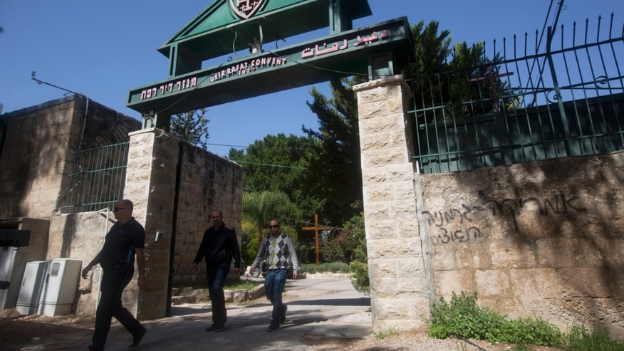 "April 1, 2014: People walk past Hebrew graffiti that reads, ""America equals Nazi Germany,"" at the Deir Rafat convent, central Israel."
