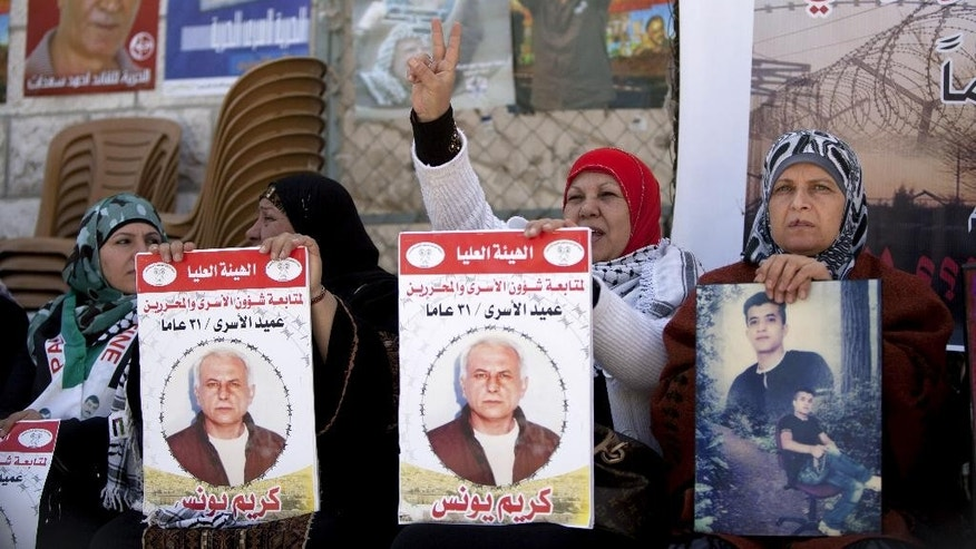 "Women hold portraits of Palestinian prisoners held in Israeli jails during a rally calling for their release in the West Bank city of Ramallah, Tuesday, April 1, 2014. Arabic on the posters read, ""Dean of prisoners, Karim Younis, 21 years in prison."" (AP Photo/Majdi Mohammed)"