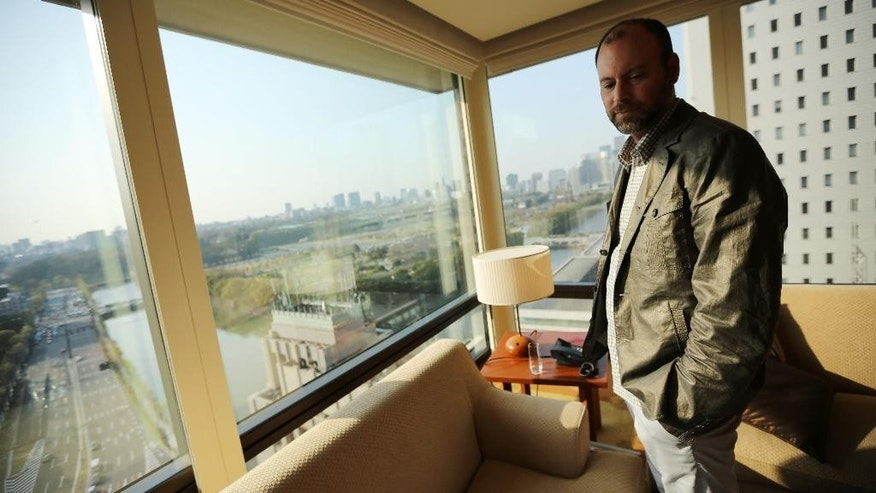 In this Tuesday, April 1, 2014 photo, Noel Biderman, chief executive of Avid Life Media Inc., which operates AshleyMadison.com., poses by a hotel room window overlooking the Imperial Palace grounds during a photo session in Tokyo. Ashley Madison, the world's biggest online hookup site for married people, works only when monogamy is the rule on the surface but, deep inside, couples want to cheat. That's why it is scoring big in Japan. (AP Photo/Eugene Hoshiko)
