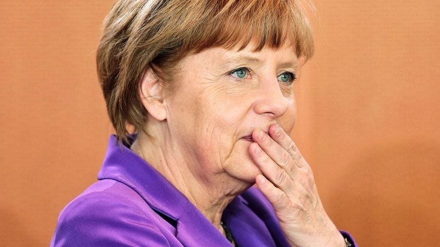 German Chancellor Angela Merkel pauses as she arrives for the weekly cabinet meeting at the chancellery in Berlin, Germany, Wednesday, April 2, 2014. (AP Photo/Markus Schreiber)