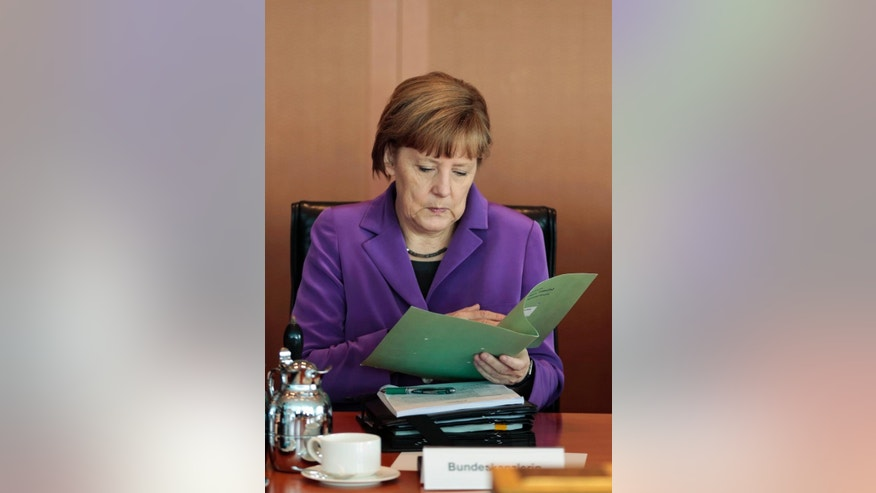 German Chancellor Angela Merkel reads in her documents after arriving for the weekly cabinet meeting at the chancellery in Berlin, Germany, Wednesday, April 2, 2014. (AP Photo/Markus Schreiber)