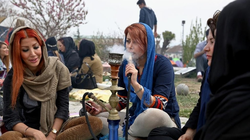 "An Iranian woman smokes a water pipe with family members observing the ancient festival of Sizdeh Bedar, an annual public picnic day on the 13th day of the Iranian new year, west of Tehran, Iran, Wednesday, April 2, 2014. Sizdeh Bedar, which comes from the Farsi words for ""thirteen"" and ""day out,"" is a legacy from Iran's pre-Islamic past that hard-liners in the Islamic Republic never managed to erase from calendars. Many say it's bad luck to stay indoors for the holiday. (AP Photo/Ebrahim Noroozi)"