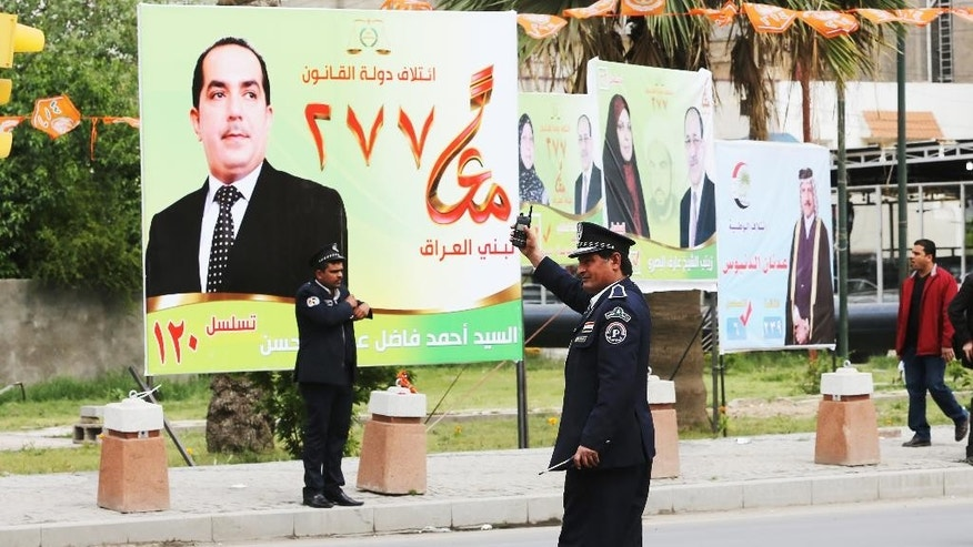 Iraqi traffic police officers control traffic in front of election campaign posters in Baghdad, Iraq,Tuesday April 1, 2014. The election campaign kicked off Tuesday with Iraqi towns and cities flooded with posters of the candidates for parliament seats on main streets and intersections. (AP Photo/Karim Kadim)