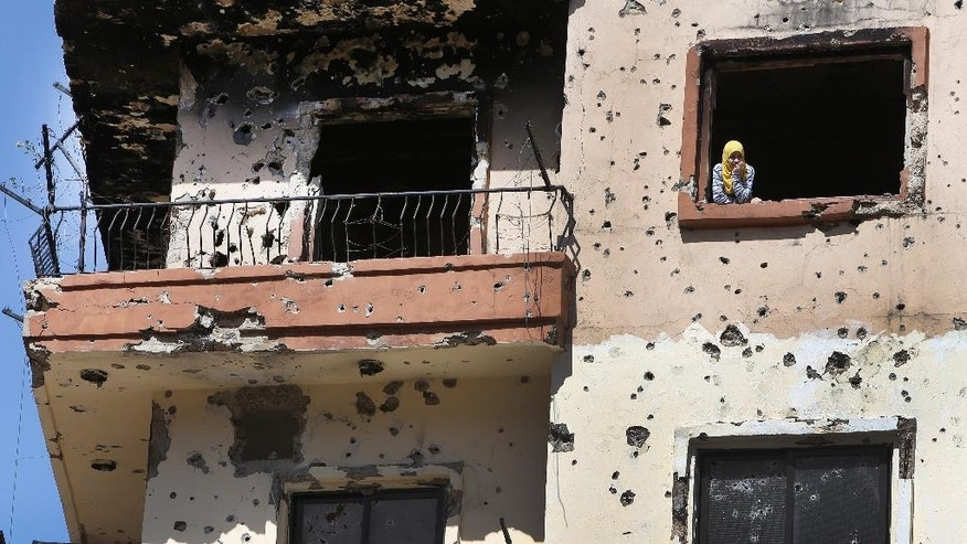 A Lebanese Sunni woman peers out of window of her house, which was damaged during clashes between pro and anti-Syrian government groups, as she looks at Lebanese army soldiers deployed in the streets of Sunni neighborhood of Bab Tabbaneh, in the northern port city of Tripoli, Lebanon, Wednesday April, 2, 2014. In a rare day of exuberant emotion, weary residents of two warring neighborhoods greeted each other with tears and cheers as hundreds of Lebanese soldiers deployed for the first time in years throughout the area, quelling violence between them that has killed at least 200 people in three years. The Lebanese army deployment in the northern city of Tripoli is the most determined plan yet by the government to bring peace to an area that was teetering into the neighboring Syrian civil war. (AP Photo/Hussein Malla)