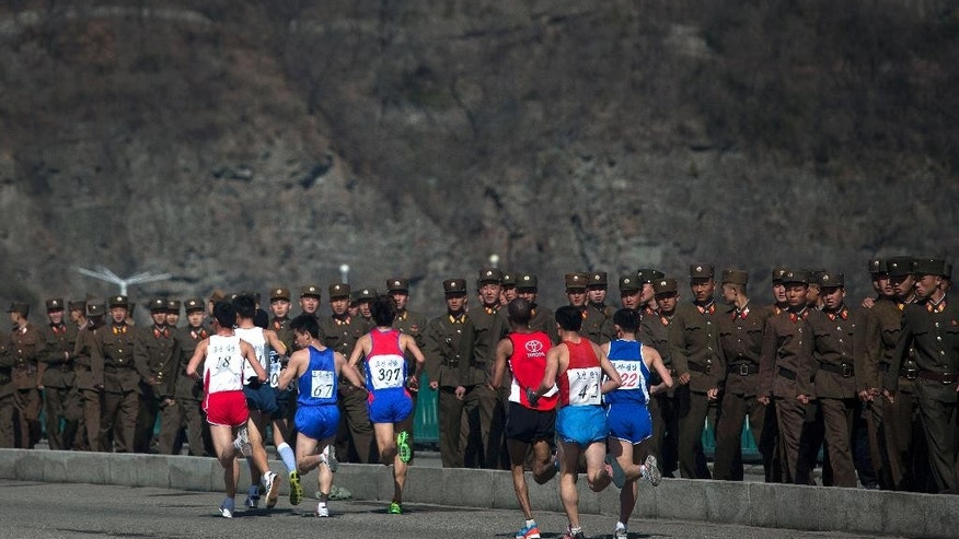 FILE - In this April 14, 2013 file photo, marathon runners pass by a long row of North Korean soldiers as they cross a bridge in Pyongyang as North Korea hosts the 26th Mangyongdae Prize Marathon to mark the birthday of the late leader Kim Il Sung on April 15. For the first time ever, North Korea is opening up the streets of its capital to runner-tourists for the annual Pyongyang marathon, undoubtedly one of the most exotic feathers in any runner's cap. Tourism companies say they have been inundated by requests to sign up for the April 13, 2014 event, which this year will include amateur runners from around the world. (AP Photo/David Guttenfelder, File)