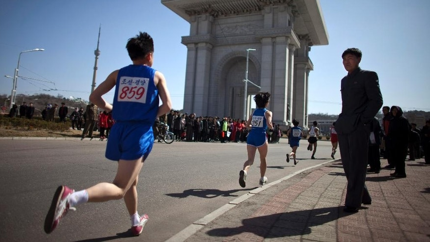 File - In this April 14, 2013 file photo, people watch runners near the Arch of Triumph in Pyongyang as North Korean hosts the 26th Mangyongdae Prize Marathon to mark the birthday of the late leader Kim Il Sung on April 15. For the first time ever, North Korea is opening up the streets of its capital to runner-tourists for the annual Pyongyang marathon, undoubtedly one of the most exotic feathers in any runner's cap. Tourism companies say they have been inundated by requests to sign up for the April 13, 2014 event, which this year will include amateur runners from around the world. (AP Photo/Alexander F. Yuan, File)