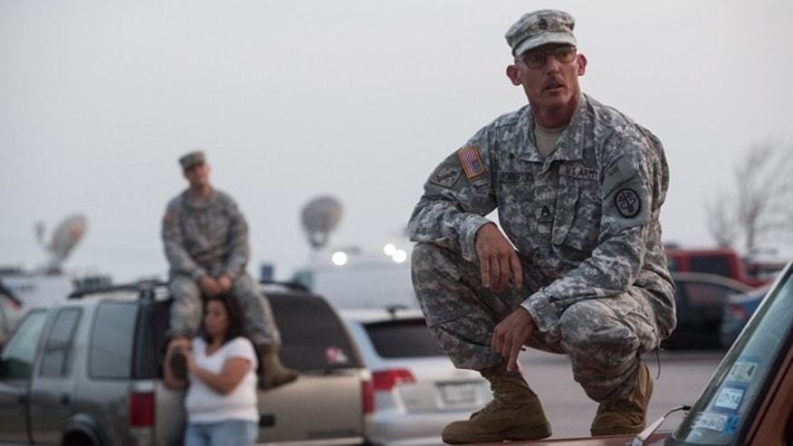 Staff Sgt. John Robertson waits in a parking lot outside of the Fort Hood military base for updates on April 2, 2014.
