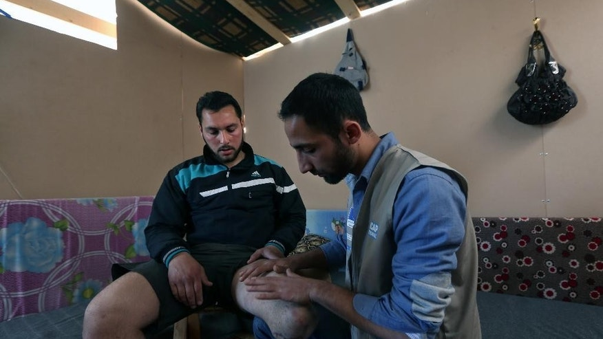 March 27, 2014: In this photo, Ziad Zehori, 24, left, who lost his leg in a Syrian government airstrike on Sept. 25, 2013, sits as Mohammed Kurdi, right, a physiotherapist for Handicap International, checks his thigh, at the Syrian refugee camp in Zahleh, in the Bekaa valley, Lebanon.