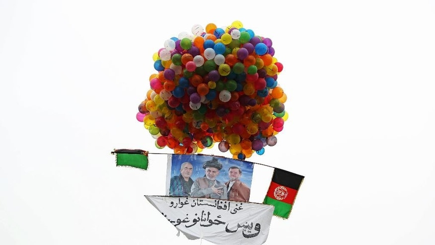 "In this photo taken on Tuesday, April 1, 2014, balloons lift a poster of Afghan presidential candidate Ashraf Ghani Ahmadzai skyward during a campaign rally in Kabul, Afghanistan. Writing on the poster reads, ""We want a reach Afghanistan, we want talented youth."" (AP Photo/Massoud Hossaini)"