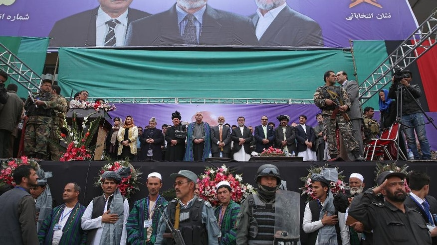 In this photo taken on Tuesday, April 1, 2014, Afghan presidential candidate Ashraf Ghani Ahmadzai,Center with orang tie, and his two vice presidential candidates listen to the national anthem during a campaign rally in Kabul, Afghanistan. (AP Photo/Massoud Hossaini)