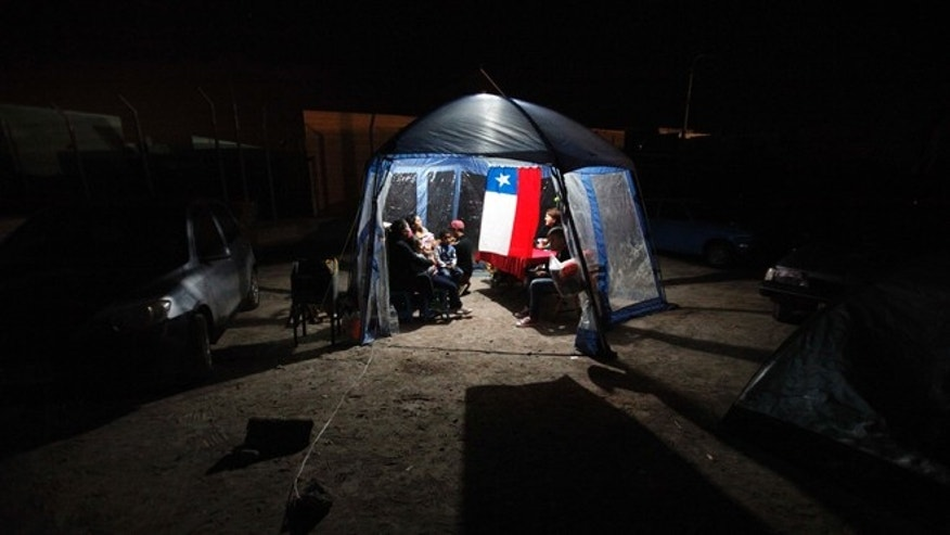 People take shelter under a tent decorated with a Chilean flag after evacuating their homes due to earthquakes in Alto Hospicio, Chile, Thursday, April 3, 2014. Coastal residents of Chile's far north spent a second sleepless night outside their homes as major aftershocks continued Thursday following a magnitude-8.2 earthquake that damaged several thousand homes and caused six deaths. (AP Photo/Luis Hidalgo)