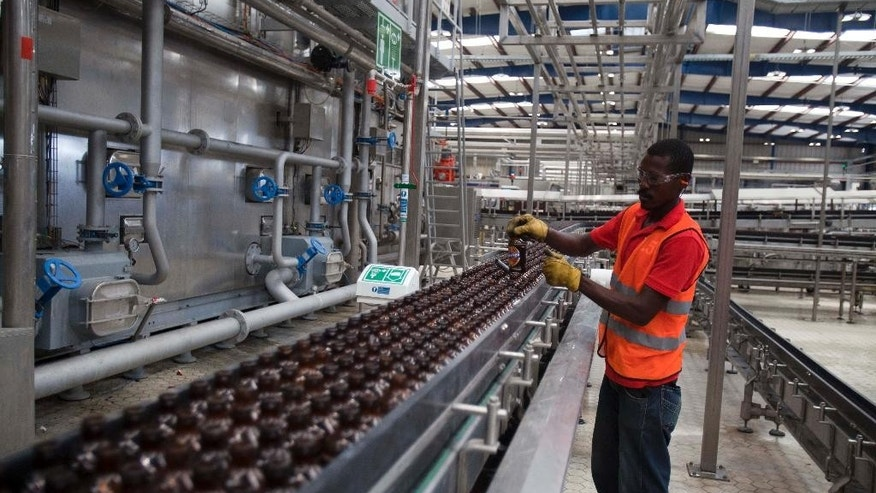 A worker cleans empty bottles of Prestige Beer at the Heineken/Brana Brewery S.A. in Port-au-Prince, Haiti, Friday April 4, 2014. Heineken NV says it is investing $100 million in the struggling Caribbean nation of Haiti. ( AP Photo/Dieu Nalio Chery)