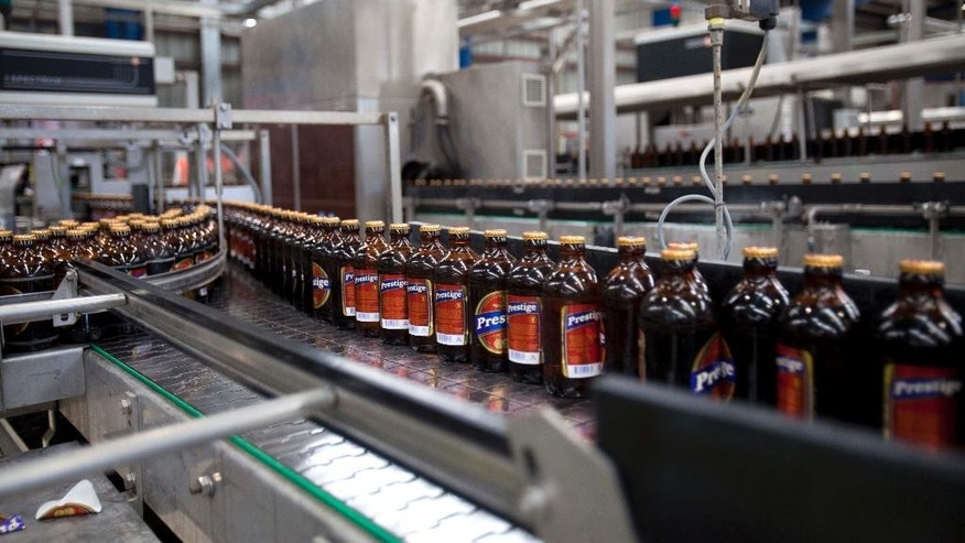 Bottles of Prestige Beer are seen at a bottling plant at the Heineken/Brana Brewery S.A. in Port-au-Prince, Haiti, Friday April 4, 2014. Heineken NV says it is investing $100 million in the struggling Caribbean nation of Haiti. ( AP Photo/Dieu Nalio Chery)