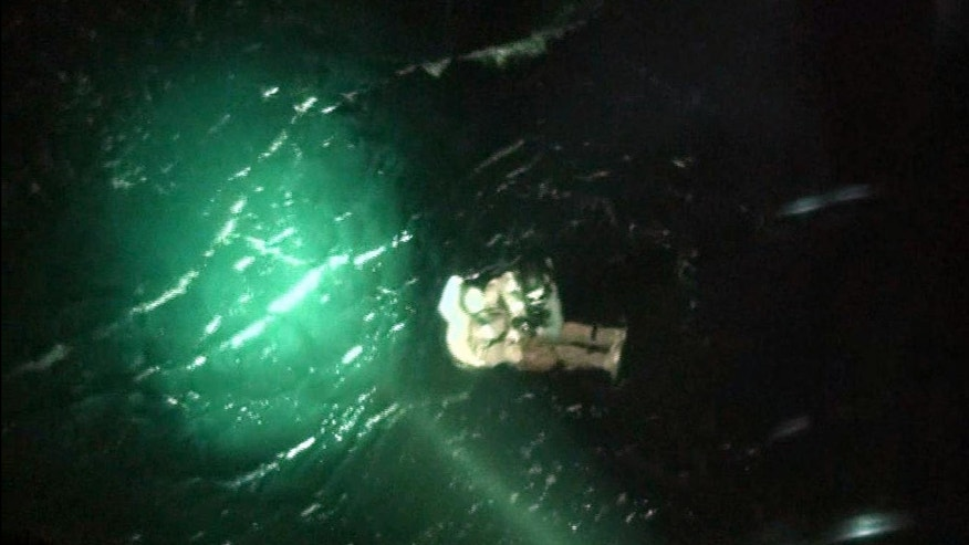 April 4, 2014 -A maritime policeman, wearing black helmet at top,  rescues a North Korean crew member of a sunken cargo ship in the sea, off Yeosu, South Korea. The Mongolian-flagged cargo ship, which was carrying 16 North Korean crew members, remains missing after it sent a distress signal early Friday in waters about 80 miles south of the southern port city of Yeosu, the coast guard said in a statement. .