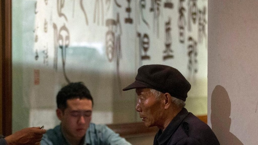 In this photo taken Wednesday, March 26, 2014, Li Zhou'er, father of Li Zhixin, rests next to a pillar at as he waits for news about Li Zhixin who is one of the passengers onboard the missing Malaysia Airlines plane, MH370 at a hotel meeting room in Beijing. The Li family wonders how to spend Saturday's annual Tomb-Sweeping Day. The three Li brothers usually visit their mother's grave in their rugged village in northeast China, but absent this year is the youngest brother - a passenger aboard the missing Malaysian airliner. (AP Photo/Ng Han Guan)