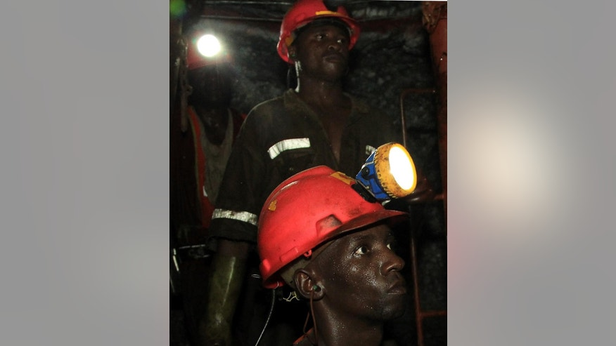 In this photo taken Thursday, Feb. 20, 2014, miners are photographed underground during a journalist's tour to the South Deep gold mine south of Johannesburg. Miners work some 2.4 kilometers  (1.5 miles) underground in 12-hour shifts, where safety is a constant concern and everyone depends on everyone else to stick to precautions.  (AP Photo/Themba Hadebe)