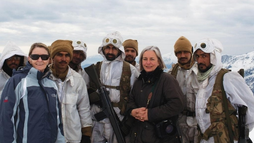 In this Feb. 2012 photo, Kathy Gannon, front left, AP special correspondent for Afghanistan and Pakistan, and veteran AP photographer Anja Niedringhaus, third right, pose with Pakistani soldiers in the remote border area opposite Afghanistan's northeastern Kunar province. The AP team was documenting Pakistan's role in fighting Islamic militants in the region. Niedringhaus, 48, was killed and Gannon was wounded on Friday, April 4, 2014 when an Afghan policeman opened fire while they were sitting in their car in eastern Afghanistan. (AP Photo)