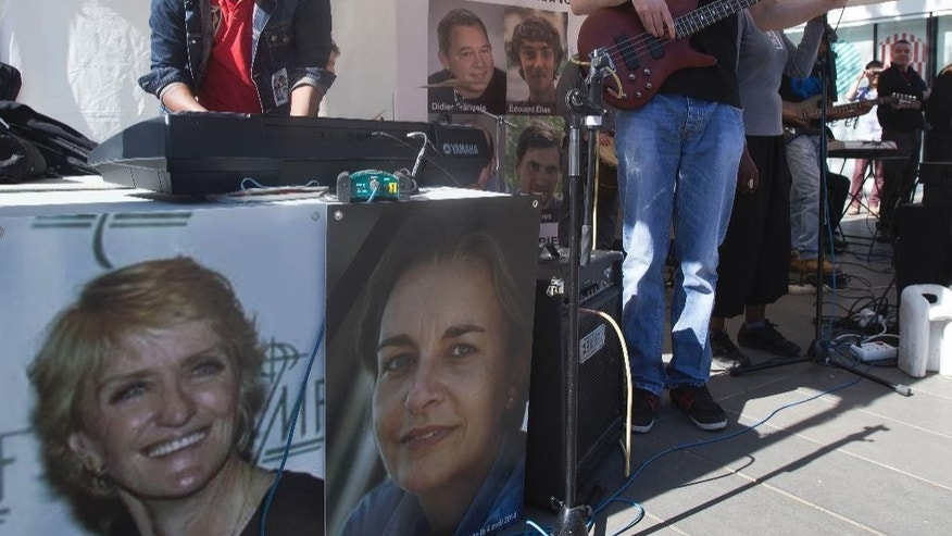 The pictures of Associated Press correspondent Kathy Gannon, who was wounded, left, and photographer Anja Niedringhaus, 48, who was killed April 4, 2014 in Afghanistan are displayed next to a playing reggae band in Paris, Saturday, April 5, 2014. Support group of the four French journalists taken hostages in Syria, Edouard Elias, Pierre Torres, Nicolas Henin and Didier Francois organized a commemoration for the late Anja Niedringhaus and AP correspondent Kathy Gannon, who was wounded in Afghanistan. (AP Photo/Michel Euler)
