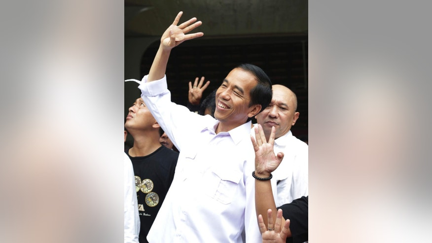 In this Sunday, March 16, 2014 photo, Indonesian presidential candidate Joko Widodo gestures during a campaign rally in Jakarta, Indonesia. Jakarta Gov. Joko Widodo, known affectionately as Jokowi, has attracted legions of supporters, especially among the young, igniting the same type of hunger for change that galvanized many previously apathetic American voters to turn out for Barack Obama in 2008. The soft-spoken former furniture producer wears simple button-down shirts with no tie or jacket and has developed a reputation of getting up close and personal with the capital's poor, from wading into floodwaters to visiting slums. (AP Photo/Achmad Ibrahim)