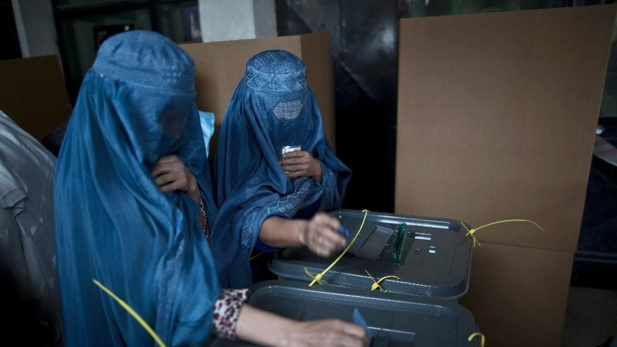 Afghan women cast their ballots at a polling station in Kabul, Afghanistan, Saturday, April 5, 2014. Afghan voters lined up for blocks at polling stations nationwide on Saturday, defying a threat of violence by the Taliban to cast ballots in what promises to be the nation's first democratic transfer of power. (AP Photo/Muhammed Muheisen)