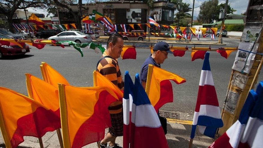 Men walk next to Costa Rican flags and political party flags, in San Jose, Costa Rica, Saturday, April 5, 2014. Costa Rica will vote on the Sunday's runoff presidential election between Juan Guillermo Solis, presidential candidate of Citizen's Action Party and ruling party candidate Johnny Araya. (AP Photo/Moises Castillo)