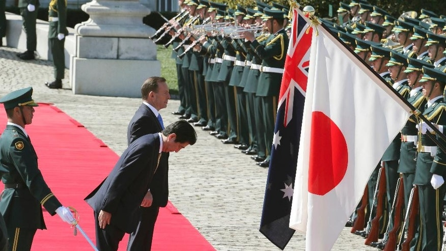 Australian Prime Minister Tony Abbott, center rear , reviews an honor guard during a welcome ceremony with Japanese Prime Minister Shinzo Abe, front, at Akasaka State Guest House in Tokyo  Monday, April 7, 2014.  Abbott is on a four-day official visit. (AP Photo/Koji Sasahara)