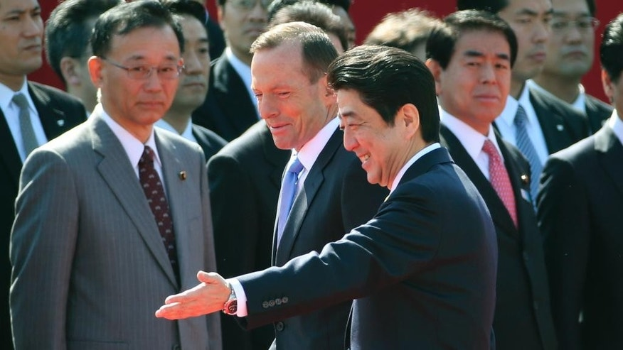 Australian Prime Minister Tony Abbott is escorted by Japanese Prime Minister Shinzo Abe during a welcome ceremony at Akasaka State Guest House in Tokyo, Monday, April 7, 2014. (AP Photo/Koji Sasahara)