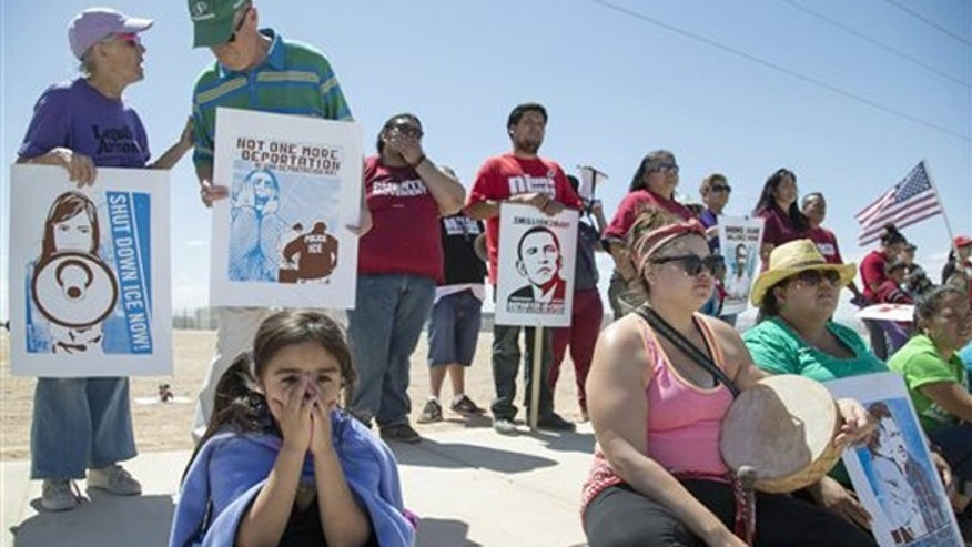 Xitlaly Hernandez, 6, on left, listens to a speech by a supporter of the immigrant advocacy group, Puente Movement, during a rally outside the immigration detention center in Eloy, Ariz., to protest the record numbers of deportations that have taken place under President Barack Obama's administration on Saturday, April 5, 2014. Immigration advocates and supporters rallied Saturday in cities across the country in a renewed effort to push President Barack Obama to put a freeze on deportations. (AP Photo/The Republic, Nick Oza) MARICOPA COUNTY OUT; MAGS OUT; NO SALES