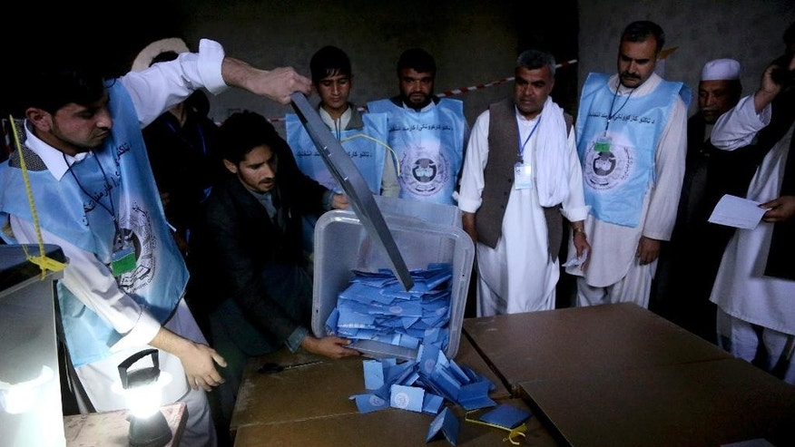 Afghan election workers remove ballots from a box at a polling station in Jalalabad, east of Kabul, Afghanistan, Saturday, April 5, 2014. The Taliban threatened to target voters and polling places, but there were few instances of violence. The vote will decide who will replace President Hamid Karzai, who is barred constitutionally from seeking a third term. Partial results are expected as soon as Sunday. (AP Photo/Rahmat Gul)