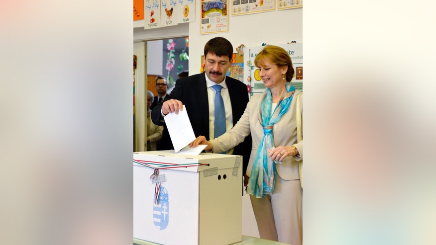 Hungarian President Janos Ader and his wife Anita Herczegh cast their vote at a polling station in Budapest during the parliamentary elections in Hungary,  Sunday April 6,  2014.  Hungary's governing party is tipped to win parliamentary elections Sunday, while a far-right party is expected to make further gains, according to polls. Prime Minister Viktor Orban's Fidesz party and its small ally, the Christian Democrats, are expected to win easily and they may even retain the two-thirds majority in the legislature gained in 2010 which allowed them to pass a new constitution, adopt unconventional economic policies, centralize power and grow the state's influence at the expense of the private sector. (AP Photo/Laszlo Beliczay)