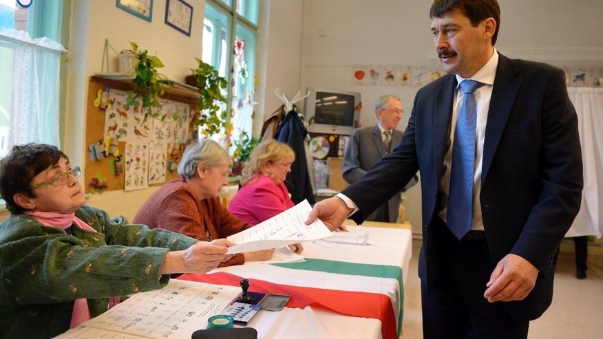 Hungarian President Janos Ader receives his ballot papers at a polling station in Budapest during the parliamentary elections in Hungary, Sunday, April 6, 2014. Hungary's governing party is tipped to win parliamentary elections Sunday, while a far-right party is expected to make further gains, according to polls. Prime Minister Viktor Orban's Fidesz party and its small ally, the Christian Democrats, are expected to win easily and they may even retain the two-thirds majority in the legislature gained in 2010 which allowed them to pass a new constitution, adopt unconventional economic policies, centralize power and grow the state's influence at the expense of the private sector.  (AP Photo/MTI,Laszlo Beliczay)