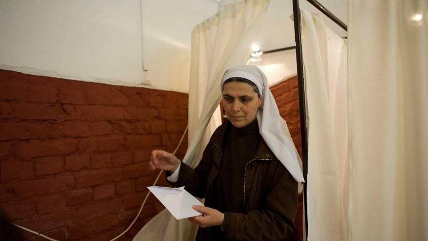 A nun exits a voting booth at a polling station in Budapest during the parliamentary elections in Hungary, Sunday, April 6, 2014.  Hungary's governing party is tipped to win parliamentary elections Sunday, while a far-right party is expected to make further gains, according to polls. Prime Minister Viktor Orban's Fidesz party and its small ally, the Christian Democrats, are expected to win easily and they may even retain the two-thirds majority in the legislature gained in 2010 which allowed them to pass a new constitution, adopt unconventional economic policies, centralize power and grow the state's influence at the expense of the private sector. (AP Photo/MTI,Bea Kallos)