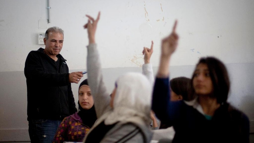 In this Thursday, April 3, 2014 photo, Palestinian Esmat Mansour, a former prisoner who was released after 20 years in Israeli jail, teaches Hebrew to students at a school in the village of Taybeh, near the West Bank city of Ramallah. Mansour was 16 when, in October 1993, he helped three older teens stab to death an Israeli man. Mansour said the time in Israeli prison changed him. (AP Photo/Majdi Mohammed)