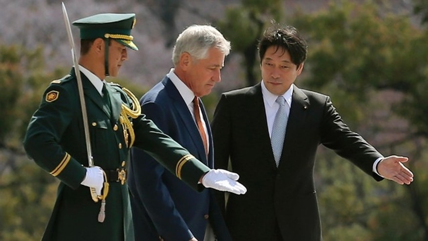 April 6, 2014: U.S. Secretary of Defense Chuck Hagel, center, is escorted by his Japanese counterpart Itsunori Onodera, right, as they inspect an honor guard at the Defense Ministry in Tokyo. (AP Photo/Eugene Hoshiko)
