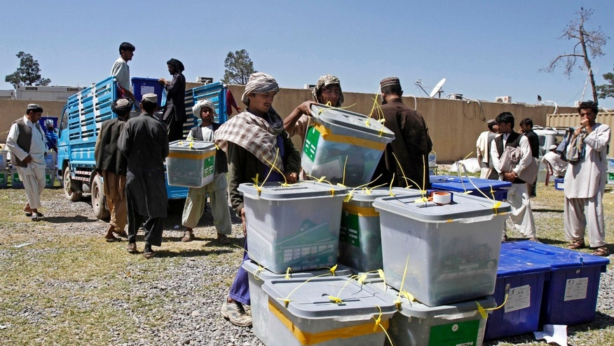 April 7, 2014 - Afghan election workers carry out a ballot box from a truck at the warehouse of the Independent Elections Commission in Kandahar, Afghanistan.
