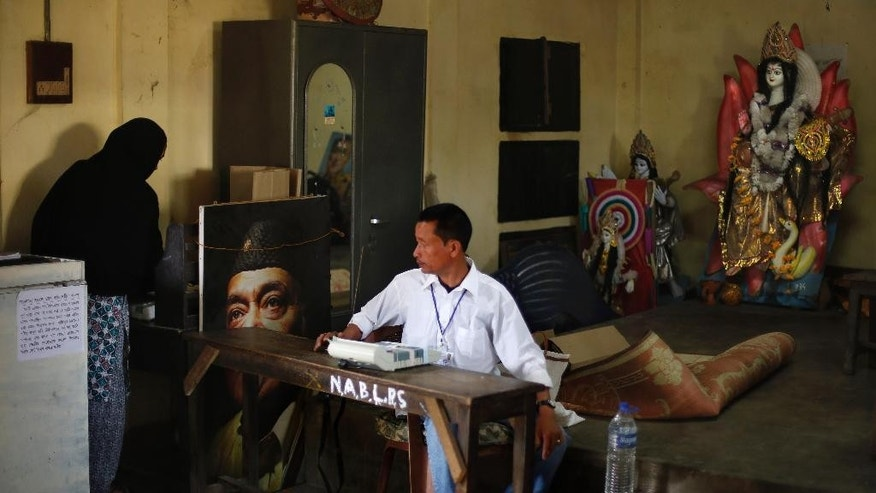 An Indian polling official watches a voter casting her vote at a polling station during the first phase of elections in Dibrugarh, in the northeastern state of Assam, India, Monday, April 7, 2014. Indians began voting Monday in the world's biggest election, with the opposition heading into the polls with strong momentum on promises of economic renewal. The country's 814 million eligible voters will vote in stages over the next five weeks. (AP Photo/Altaf Qadri)