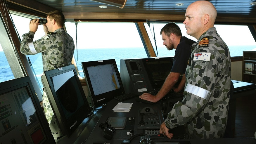 In this April 5, 2014, photo provided by the Australian Defense Force, Commander James Lybrand, right, watches from the bridge with Captain Nick Woods, Master of the ship, left, as they tow a pinger locator behind the Royal Australian Navy ship Ocean Shield in the southern Indian Ocean. Ocean Shield, which is carrying high-tech sound detectors from the U.S. Navy, is investigating a sound it picked up. (AP Photo/Australian Defense Force, Bradley Darvill) EDITORIAL USE ONLY