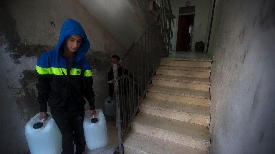 In this April 3, 2014 photo, a Palestinian carries water tanks to his house in Shuafat, east Jerusalem. Tens of thousands of Palestinians in east Jerusalem have been without water for more than a month, victims of a decrepit and overwhelmed infrastructure and caught in a legal no-man's land. Their district is technically part of Jerusalem municipality, but on the other side of the massive Israeli-built West Bank separation barrier, so Israeli services there are sparse yet Palestinian officials are barred for operating. With the scorching summer approaching, residents are growing increasingly desperate. (AP Photo/Sebastian Scheiner)