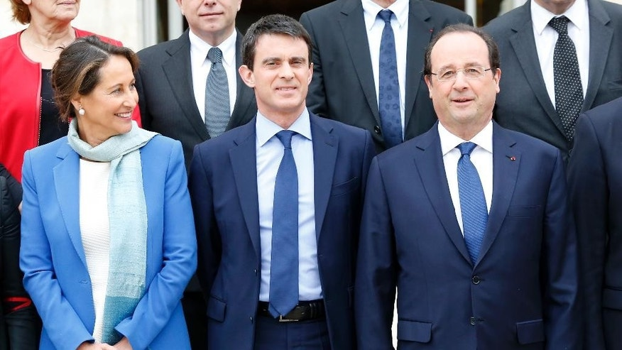 French President Francois Hollande, right,  new French Prime Minister Manuel Valls, center, and  Environment and Energy minister Segolene Royal pose during the family picture after the first weekly cabinet meeting after municipal elections, at the Elysee Palace in Paris, Friday, April 4, 2014. President Francois Hollande shook up the government this week after his Socialist Party suffered an electoral defeat in nationwide municipal elections. Among two new faces in the Cabinet is Segolene Royal, a longtime politician and mother of Hollande's children, as environment and energy minister. (AP Photo/Jacques Brinon)