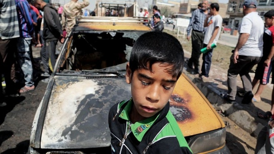 April 9, 2014: Civilians inspect the site of a car bomb attack in Baghdad's Sadr City neighborhood, Iraq.